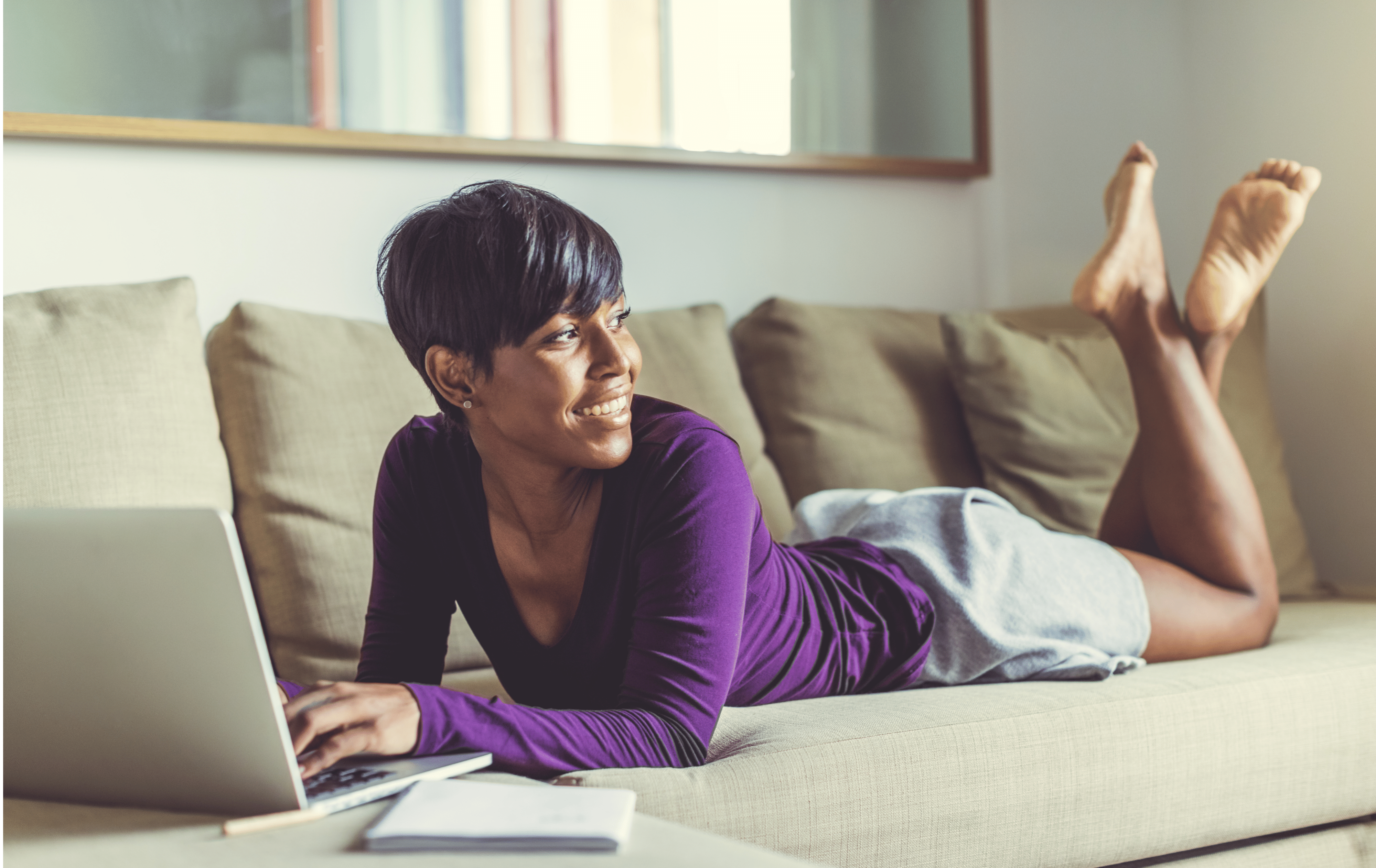 A person of color is laying on their stomach atop a beige couch. They are wearing a long sleeve purple shirt with gray sweatshorts: their hands are gently resting on the keyboard of their laptop as they look away from the camera and out the window. Their hair is short and dark and their dreamy smile is fixed on what they are seeing outside of the camera shot.