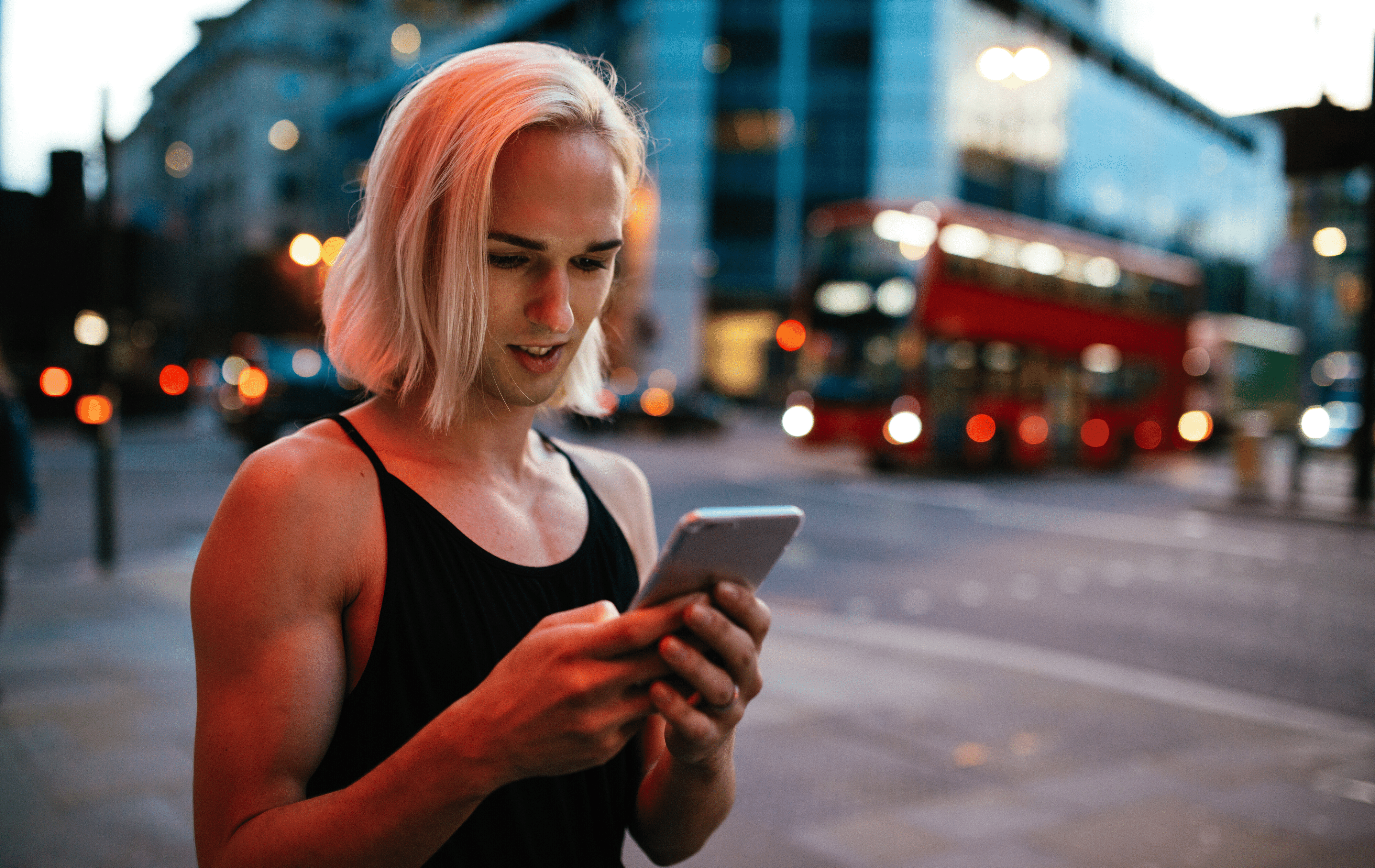 A non binary person with straight, soft blonde hair to their shoulders looking down at the phone screen they are holding in their hands. They are on a busy city street at dusk with a bus and traffic lights behind them. Their facial expression is engaged with what they are looking at with a slight, open-lipped smile.