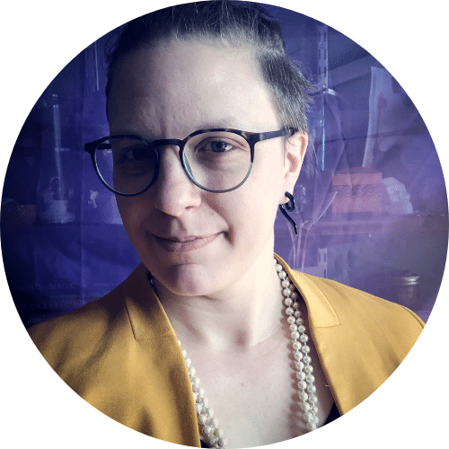 Photo of Juniper Caldera: wearing a canary yellow blazer and long, thick strand of pearls. They are wearing glasses with their hair tied on the top of their head with a close lipped smile.