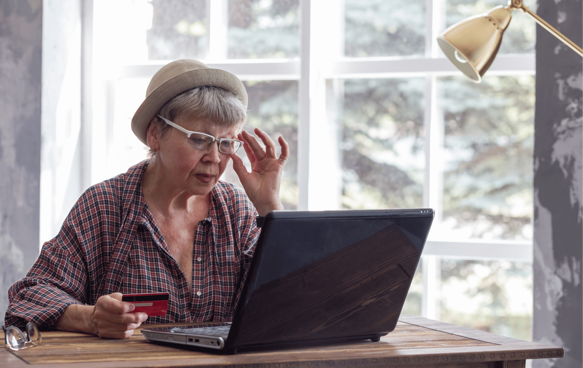 An older person wearing a cute hat in an oversized flannel shirt is sitting at a table with a laptop holding a credit card on a bright day. They are adjusting their glasses with the other hand while looking intently at the screen.